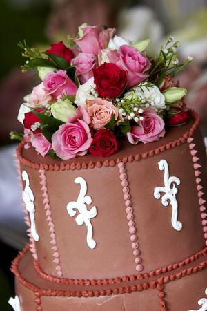 The top of a wonderful wedding cake is covered by red, white, and pink roses photo