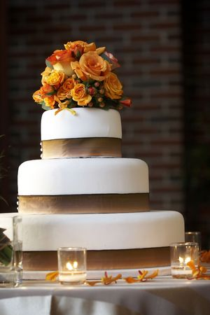 wedding food: a wedding cake lit a little hot (bright) from the side and topped with reddish orange flowers. There are candles in the foreground that are out of focus, with the focus on the cake and flowers. There is a dark background that would be easily seperated fro