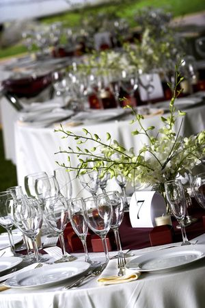 receptions: A table setting for a formal dinner or a wedding. This image has a VERY shallow depth of field, if you want more in focus, dont choose this photo! There are empty glasses and plates on the table, a number 7 placement card, and little notes to guests that