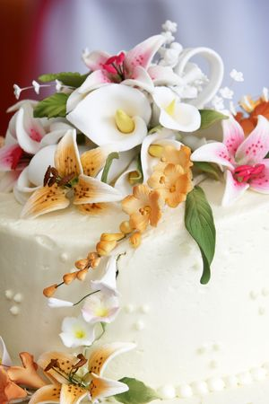 georgeous: The top of a beautiful wedding cake with a georgeous flower arrangement on top.