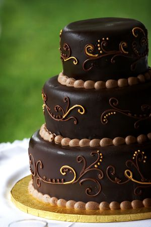 A multi layered chocolate coffee flavored wedding cake with a blurred green background and a detailed design