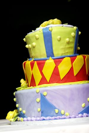 An over the top, super crazy layered wedding or party cake in mixed colors, including red, yellow, blue, purple, and green photo