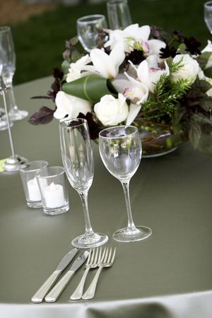 a typical dinner table setting, with a shallow depth of field with the focus on the glasses and silverware, flowers out of focus Stock Photo
