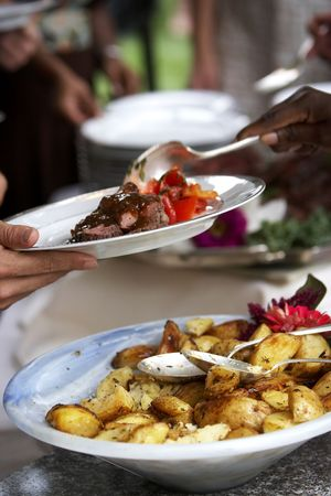 catering: Food being served at a buffet style event, there is movement in the spoon as the food is being dumped onto the plate. Stock Photo