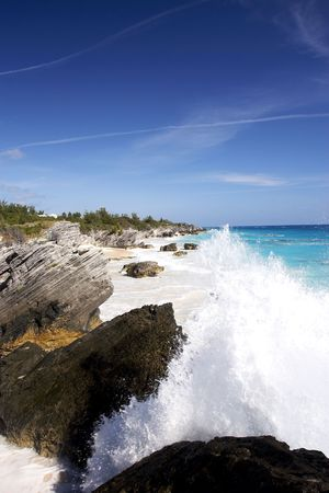 Waves crashing in the foreground of a beautiful tropical coastline