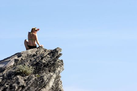 Woman sitting on a rock and looking. Blue sky