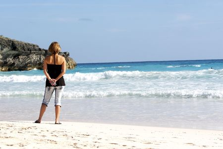 Woman looking out on the crashing ocean, cell phone behind her back