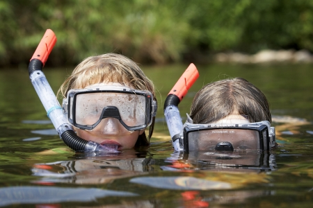two small and young children playing at the river on a warm sunny day. they are wearing snorkling equiptment and are in the water
