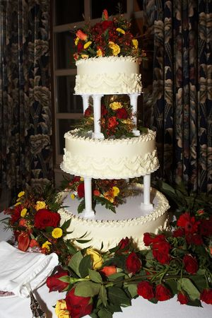 a three tiered yellow wedding cake with roses photo