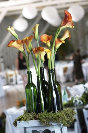 centerpiece: beautiful flowers in old fashion green bottles on moss. The are decorations for a wedding Stock Photo