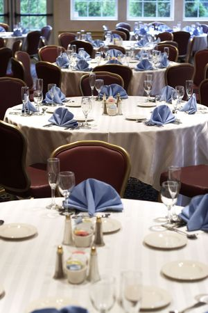 tables set for fine dining at a wedding or event. This image has a shallow depth of field, with the focus on the center table