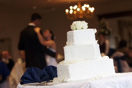 a white wedding cake with neat little swirl details and silver candy buttons, bride and groom are dancing in the background