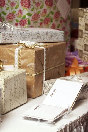 A blank guest book at a wedding or birthday with presents on a table, wrapping says: Like the circle of a ring love is forever
