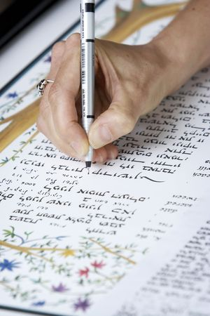 signing a jewish ketubah document during a wedding ceremony photo