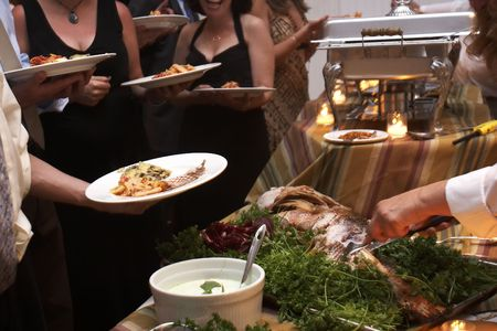 Food being served buffet style during a wedding event. This was shot witha slow shutter speed, and there is some movement noticeable.