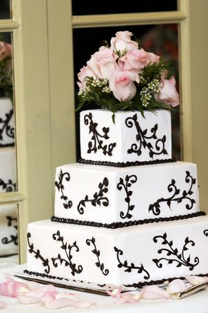 a wedding cake with pink roses sitting on a shelf with a mirror