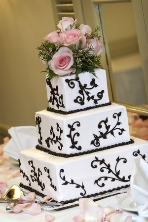 a wedding cake with pink roses. very shallow depth of field