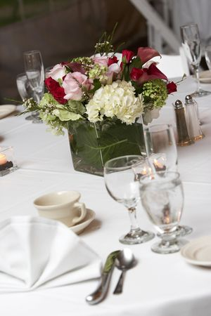 forground: table setting for a wedding or dinner event, very shallow depth of field with the focus on the flowers, blurry forground.