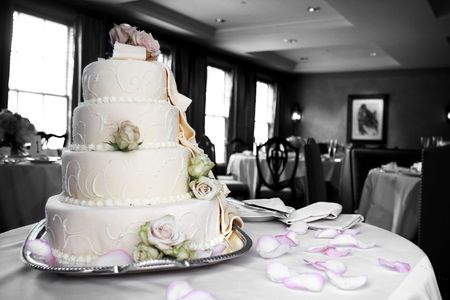 customs and celebrations: A wedding cake with the cake and pink flower petals in color and the rest of the photo in black and white. Stock Photo