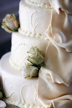 Wedding cake detail with flowing sugar folds and dried flowers decorating it. This wedding cake is a creamy off white almost yellow color. Very shallow depth of field. Stock Photo