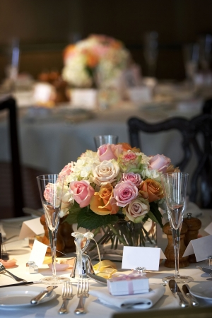 caterer: table setting for a wedding or dinner event, very shallow depth of field with the focus on the flowers, blurry background. Stock Photo