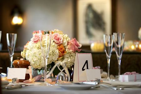 cloth halls: table setting for a wedding or dinner event, very shallow depth of field with the focus on the flowers, blurry background and blank name cards