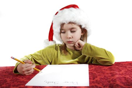 A young girl child writing her wish list to santa. Dear Santa on her otherwise blank piece of paper. Red table cloth, with an isolate white background. Stock Photo