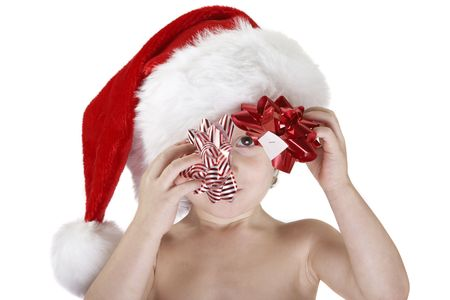A young child wearing a santa hat and holding a reb christmasbow and a red & white christmas bow. Looking at the camera though the bows, the white sticker underneath is visible. Isolated white background