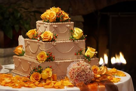 A chocolate wedding cake surrounded by rose petals and a brides bouquet of flowers. Sitting an a table with a fire in the background. There are orange roses and nice details on the cake. Standard-Bild