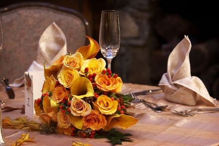 Brides wedding bouquet of flowers sitting on a table set for fine dining during a banquet event. Stock Photo
