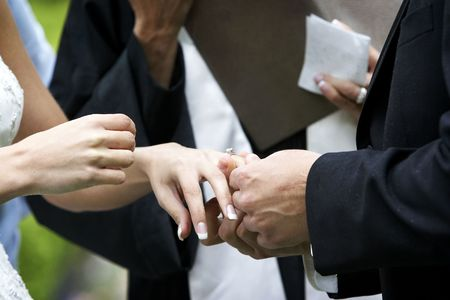 Putting the ring on the bride during a wedding ceremony Stock Photo