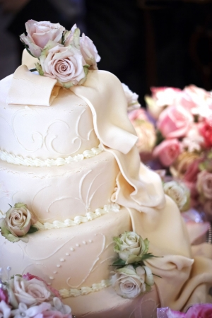 cater: Wedding cake with thick creamy frosting and dried roses as decorations. This image has a shallow depth of field Stock Photo