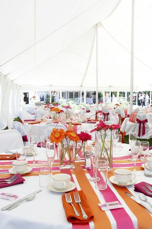 wedding tables set for fine dining during an event outside under a large white tent