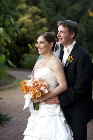 Wedding bride and her new husband. She is holding her beautiful bridal bouquet of flowers. They are looking away from the camera. Stock Photo