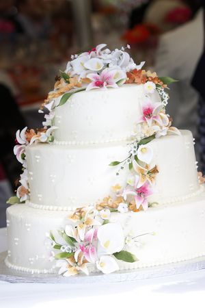 This is a white wedding cake with what appears to be real flowers. The flowers are made entirely of sugar and the whole thing is edible.