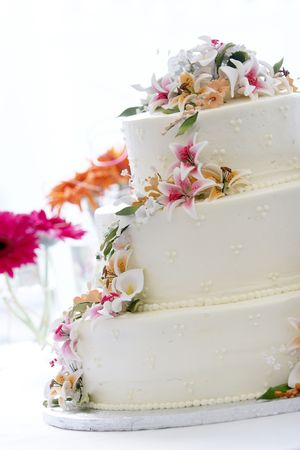 caterer: a beautiful wedding cake with a georgeous candy flower arrangement. This image is heavily back lit with a blown out background Stock Photo