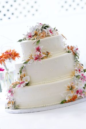 a beautiful wedding cake with a georgeous candy flower arrangement. This image is heavily back lit with a blown out background Stock Photo