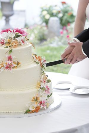 A wonderful wedding cake with the bride and groom cutting the cake with a long knife. The flowers look real, but are really edible sugar flowers!