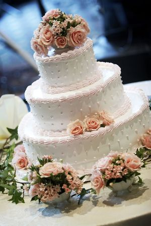 wedding cake: A three tiered wedding cake, shallow depth of field with the focus on the center of the cake. Pink roses on top.