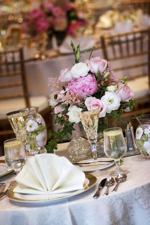 tables set for fine dining during a wedding event. Shallow depth of field, focus on the bouquet of flowers