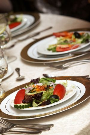 tables set for fine dining during a wedding event. Plates of salad as an appetizer Stock Photo