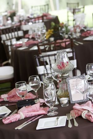cater: tables set for fine dining during a wedding event. Shallow depth of field, focus on items in the center of the table Stock Photo