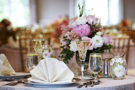 dining table and chairs: tables set for fine dining during a wedding event. Shallow depth of field, focus on items in the foreground