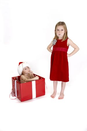 naughty or nice: An angry sister and her gift wrapped brother, She has a mad expression Stock Photo