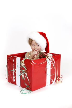 A young child sitting in a christmas box with a naughty look in his eyes. Stock Photo