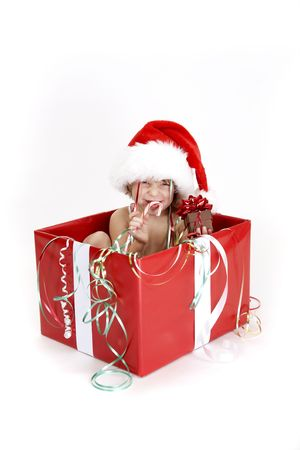 A young child sitting in a christmas box laughing with a candy cane