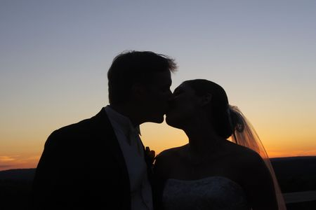 A bride and groom kissing with a sunset in the background Stock Photo