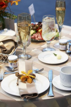 Details of a wedding table set for fine dining with an orchid
