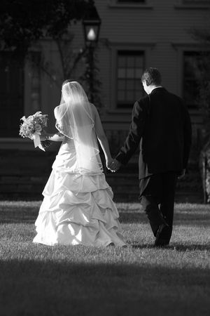 Bride and groom holding hands and walking away from the camera. Black and white photo.