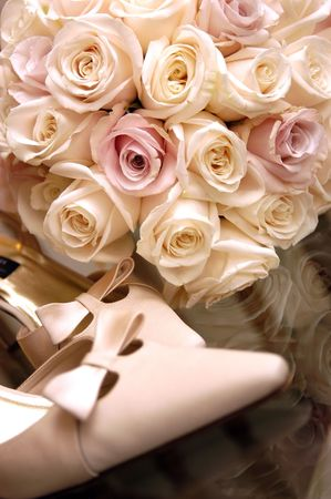 Wedding bouquet and shoes. Sharpness is on the flowers, shallow depth of field, focus on the shoes Stock Photo